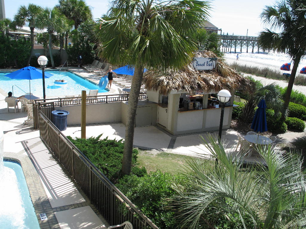 Holiday Pavilion Oceanfront Resort Family Vacation Rental Condo - Tropical Paradise Beach & Pool Bar, heated outdoor pool, children's activity pool with sprinkling mushroom, beachfront with a view of Pier 14