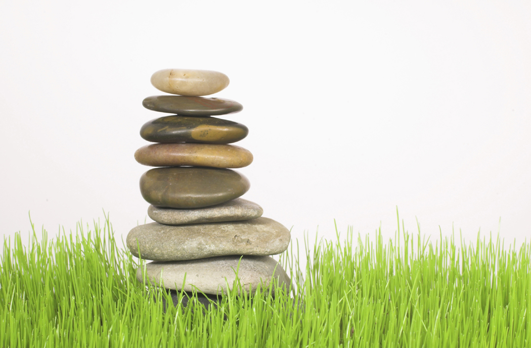 rocks balanced on top of each other and set on grass