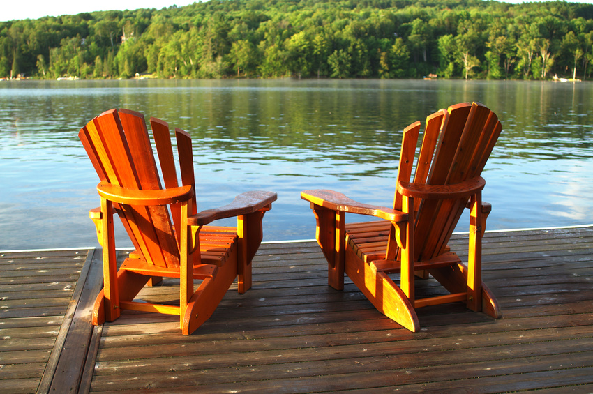 Two chairs on a deck facing a lake