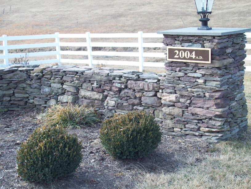 Dry stacked stone estate entrance wall and boxwood bed
